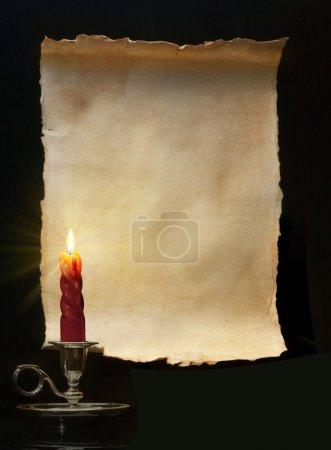 Foto de Rollo de papel Vintage encendió una vela en fondo negro - Imagen libre de derechos