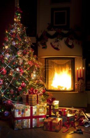 Foto de Cajas de regalo de Navidad y el árbol de Navidad en el interior con chimenea - Imagen libre de derechos