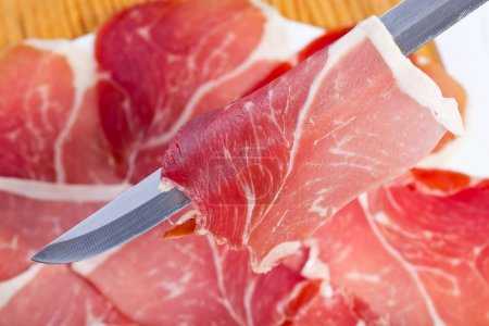 Photo for Cut slices of ham with a carving knife on the plate out of focus - Royalty Free Image