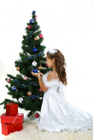 Little beautiful girl near a christmas tree isolated on a white background