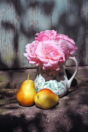 Photo for Beautiful vase with pink roses and pears in the garden - Royalty Free Image
