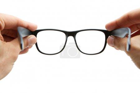 Human hands holding retro style eyeglasses