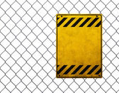 Empty yellow plate at chainlink fence