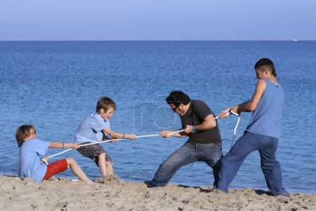 Photo for Tug of war game, kids playing at beach with unfair advantage - Royalty Free Image