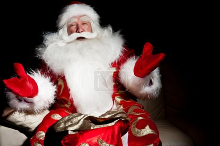 Photo for Santa sitting with a sack indoor at dark night room - Royalty Free Image