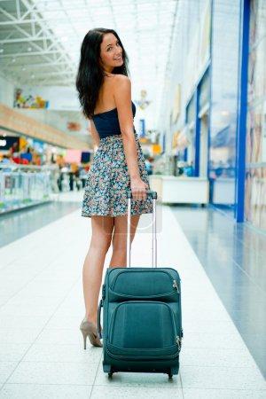 Photo pour Jeune femme assez élégante avec des bagages à l'aéroport international. En attente de son vol dans une zone commerçante libre d'impôt . - image libre de droit