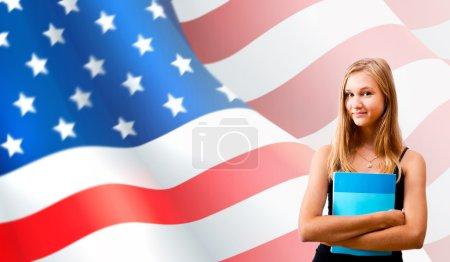 Photo pour Portrait d'une jolie jeune femme tenant un livre dans ses bras. USA Drapeau sur fond. Concept d'éducation internationale. Espace de copie - image libre de droit