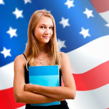 Photo pour Portrait d'une jolie jeune femme tenant un livre dans ses bras. USA Drapeau sur fond. Concept d'éducation internationale - image libre de droit
