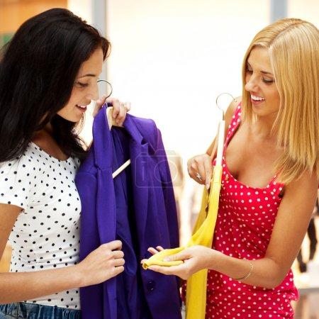 Foto de Grupo de dos hermosas mujeres compras probándose ropa en centro comercial en el interior - Imagen libre de derechos