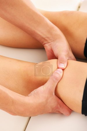 Photo for A picture of a physio therapist giving knee massage over white background - Royalty Free Image