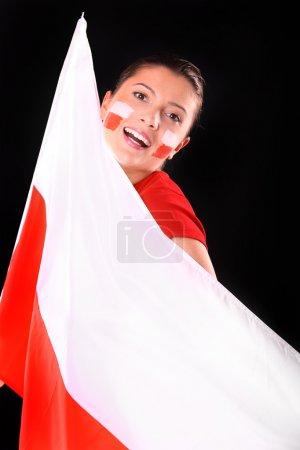 Photo pour Une photo d'un fan de sexe féminin polonais heureux avec le drapeau sur fond noir. - image libre de droit