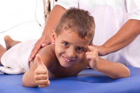 Smiling boy with the physiatrist in therapy
