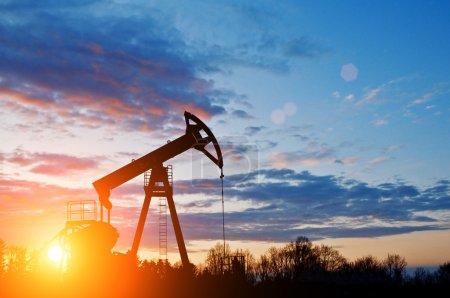 Photo pour Silhouette de pompe à huile sur le ciel couchant - image libre de droit