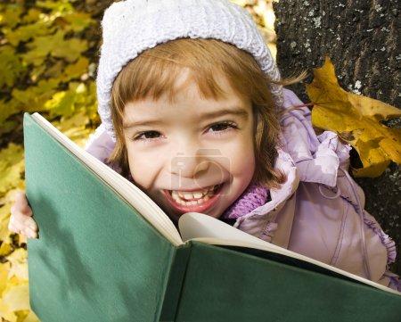 Photo pour Fille lit un livre dans un parc - image libre de droit