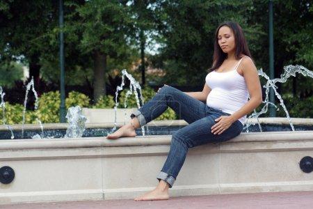 Photo pour Une charmante jeune femme multiraciale avec les yeux fermés, enceinte de cinq mois se trouve au bord d'une fontaine extérieure. - image libre de droit