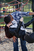 Romantic Couple Kissing on a Playground (1)
