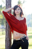 Beautiful Young Woman Leaning on a Tree (2)