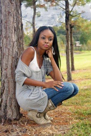 Photo pour Une jeune femme extraordinairement belle s'appuie contre un arbre de pin à l'extérieur. - image libre de droit