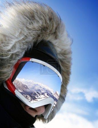 Photo pour Gros plan des lunettes de ski d'un homme au reflet des montagnes enneigées - image libre de droit