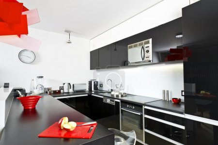 Photo for Moder black and white kitchen interior with red lamp - Royalty Free Image