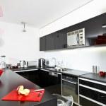 Moder black and white kitchen interior with red la...