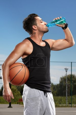 Photo for Young man drinking mineral water on a basketball court - Royalty Free Image
