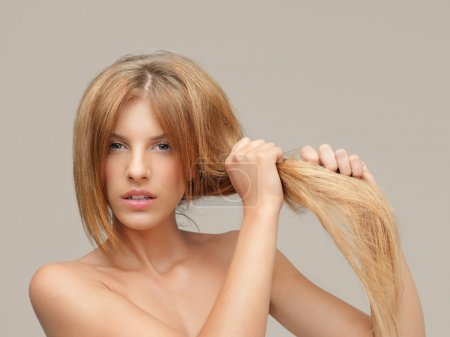 Photo for Young woman pulling damaged hair both hands - Royalty Free Image