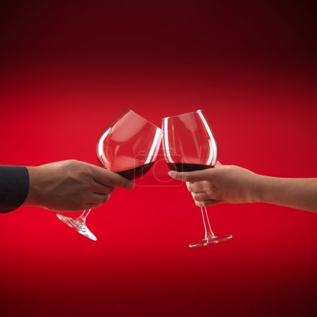Photo for Hands of man and woman holding glasses of red wine, toasting, on red background - Royalty Free Image