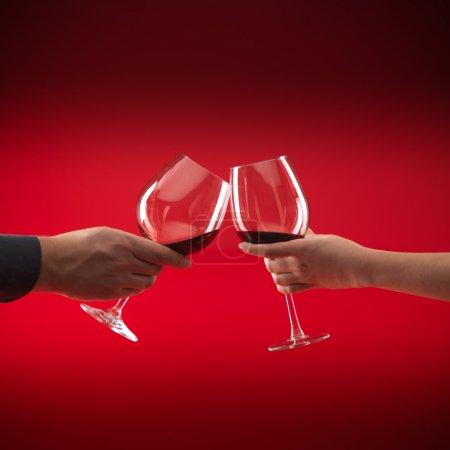 Photo pour Mains d'homme et femme tenant des verres de vin rouge, le grillage, sur fond rouge - image libre de droit
