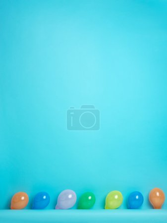 Blue background with colored balloons in row