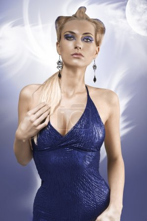 Photo pour Coup de mode d'une fille blonde avec un up-do créatif et portant une robe bleue métallique - image libre de droit