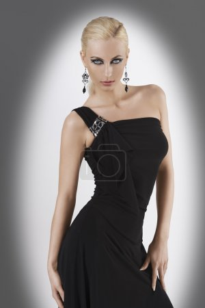 Photo for Blond attractive young woaman in black dress and black earring looking in camera with strong and sexy eyes and wit sexy pose looking towards the camera - Royalty Free Image