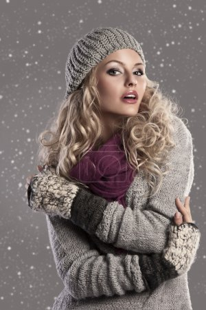 Photo for Attractive young woman in a winter fashion shot wearing a wool cap, a grey woolen sweater and a purple scarf - Royalty Free Image