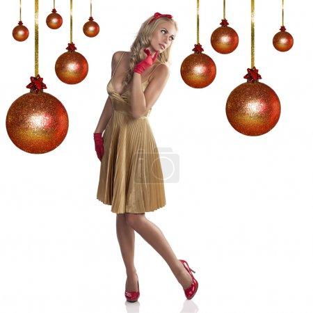 Photo pour Mode fille de Noël portant une robe dorée, gants rouges et un arc de cheveux rouges dans ses longs cheveux blonds - image libre de droit
