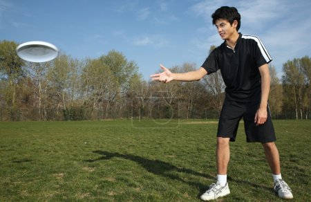 Photo for Young man playing frisbee in the park - Royalty Free Image