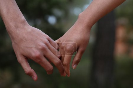Photo for Lovers couple holding hands in a forest (summer/spring) - Royalty Free Image