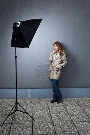Photo pour Jolie jeune mannequin femme caucasienne photographiée sur place éclairée par un stroboscope dans une softbox - image libre de droit