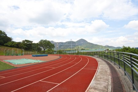 Sports stadium with running track at day