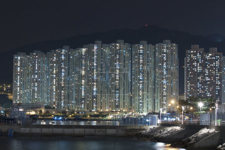 Hong Kong apartment blocks at night, showing the packed conditio