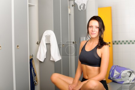 Locker room young sportive woman sitting smiling
