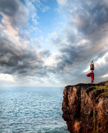 Photo for Woman doing yoga vrikshasana tree pose on the cliff near the ocean with dramatic sky at background in India - Royalty Free Image
