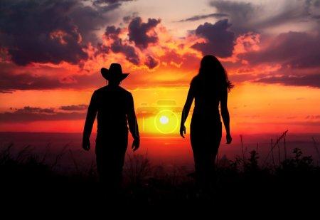 Photo pour Silhouette de jeune couple marchant en plein air au fond de coucher de soleil ciel dramatique. homme au chapeau de cowboy et une femme est proche - image libre de droit
