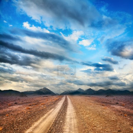 Photo for Road to the mountains through the desert at sky with clouds - Royalty Free Image