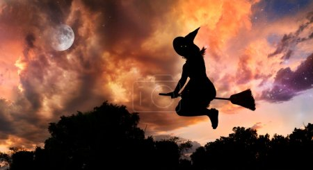 Halloween witch silhouette with glowing eyes flyin...