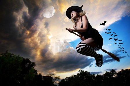 Photo pour Méchante sorcière volant sur balai avec des chauves-souris derrière elle et la lune à proximité dans le ciel dramatique du soir fond. Espace libre pour le texte - image libre de droit