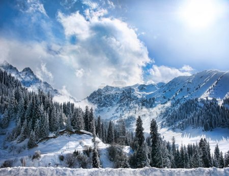 Photo pour Vallée de montagnes enneigées d'hiver avec brouillard et soleil en chumbulak, almaty, kazakhstan - image libre de droit