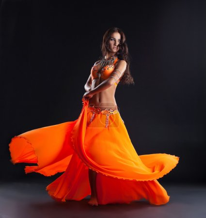 Photo for Beauty young woman dance in orange veil arabic style costume - Royalty Free Image