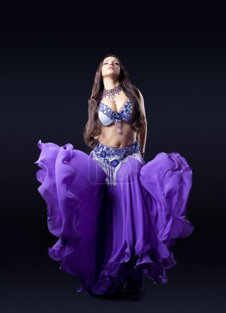 Beauty dancer posing in dark with fly purple veil