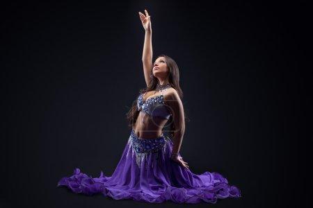 Arabia dancer posing in dark - oriental costume