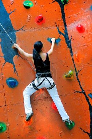 Girl climbing on a climbing wall